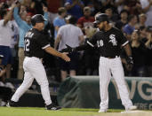 Chicago White Sox's Leury Garcia, right, celebrates with third base coach Nick Capra after hitting a three-run triple against the Toronto Blue Jays during the eighth inning of a baseball game Saturday, July 28, 2018, in Chicago. (AP Photo/Nam Y. Huh)