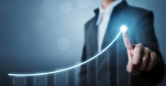 Business man pointing at an arrow on a graph to symbolize growth
