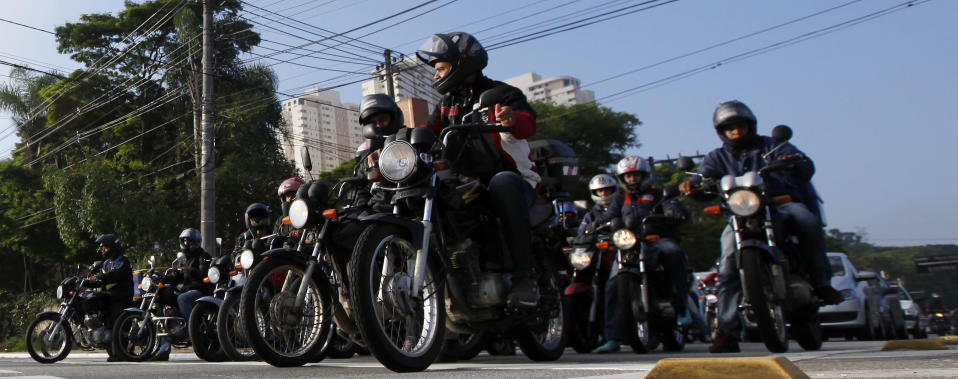 Motorcyclists move to the front of traffic waiting for a green light at an intersection in Sao Paulo, November 22, 2012. Dying at the rate of three per day, according to official statistics, Sao Paulo's approximately 200,000 registered motorcycle couriers, nicknamed either motoboys or mad dogs, are the terror of drivers. Motoboys in the city bully drivers into giving them the right of way as they race along the corridors formed between the rows of vehicles stuck in heavy traffic, making them their exclusive high speed corridors. Picture taken November 22, 2012. REUTERS/Paulo Whitaker (BRAZIL - Tags: SOCIETY TRANSPORT)