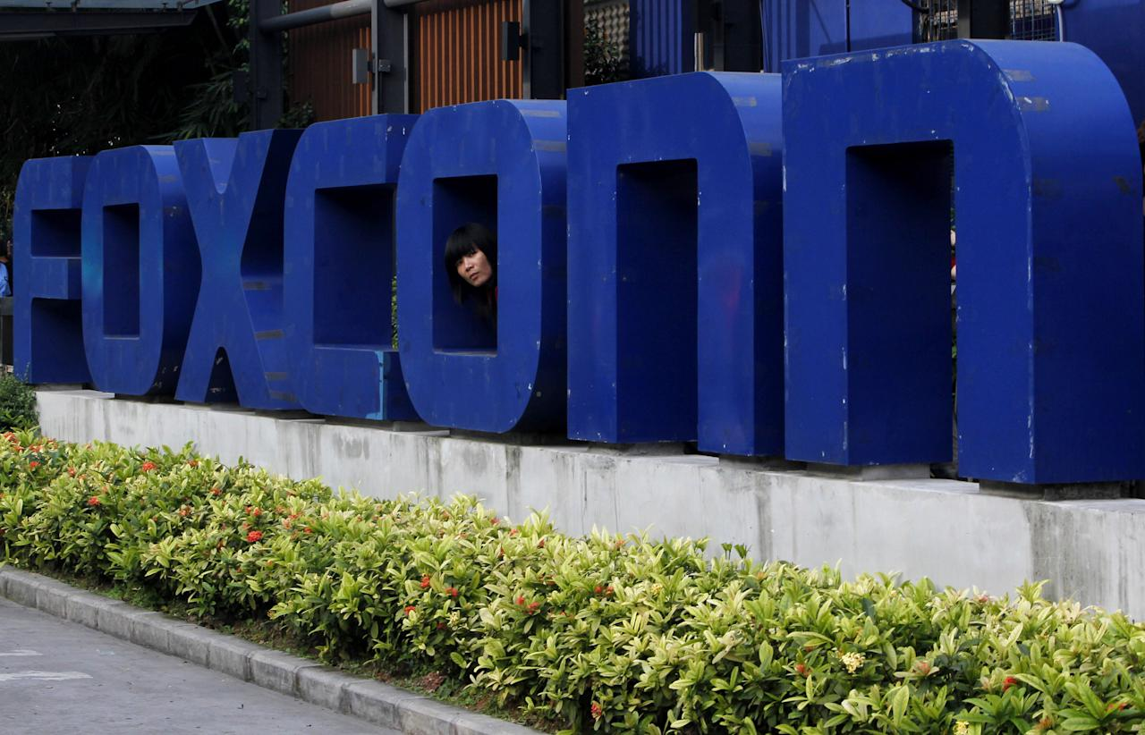 <p> FILE - In this Thursday, May 27, 2010, file photo, a worker looks out through the logo at the entrance of the Foxconn complex in the southern Chinese city of Shenzhen. Taiwanese electronics maker Foxconn's plan to build a display panel factory in the U.S. has sparked a flurry of lobbying by states vying to land what some economic development officials say is a once-in-a-generation prize. (AP Photo/Kin Cheung, File) </p>