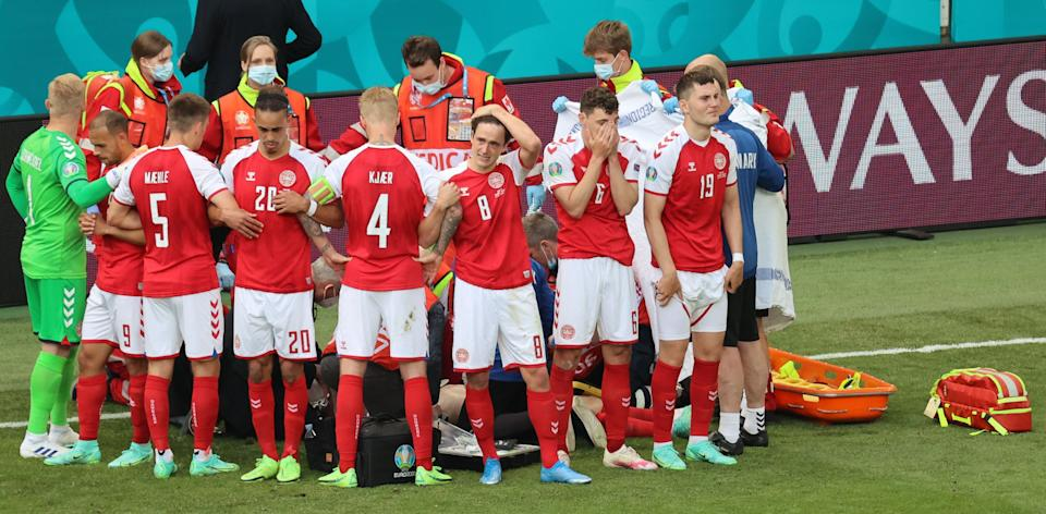 Denmark's players gather as paramedics attend to midfielder Christian Eriksen (not seen) during the UEFA EURO 2020 Group B football match between Denmark and Finland at the Parken Stadium in Copenhagen on June 12, 2021. (Photo by WOLFGANG RATTAY / various sources / AFP) (Photo by WOLFGANG RATTAY/AFP via Getty Images) (Photo: WOLFGANG RATTAY via Getty Images)