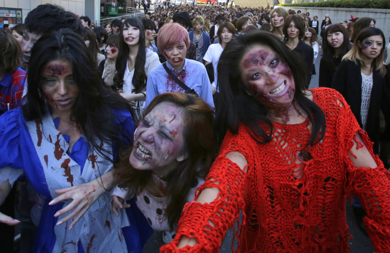 Participants wearing zombie makeup, perform during a Halloween event at Tokyo Tower in Tokyo, Thursday, Oct. 31, 2013. (AP Photo/Shizuo Kambayashi)