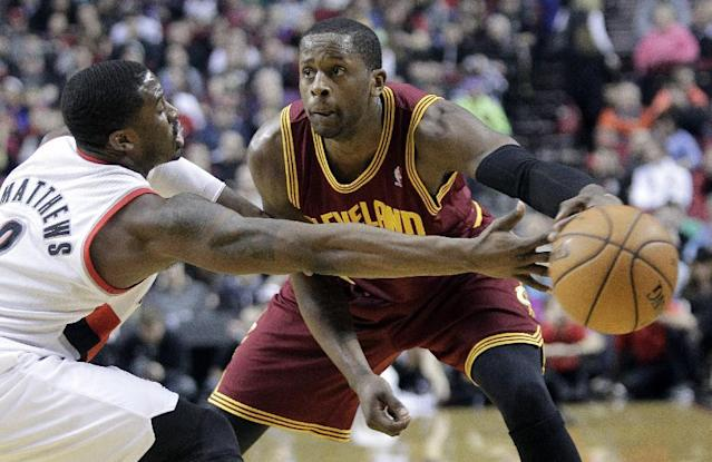 Cleveland Cavaliers guard C.J. Miles, right, passes inside against Portland Trails Blazers guard Wesley Matthews during the first half of an NBA basketball game in Portland, Ore., Wednesday, Jan. 15, 2014. (AP Photo/Don Ryan)