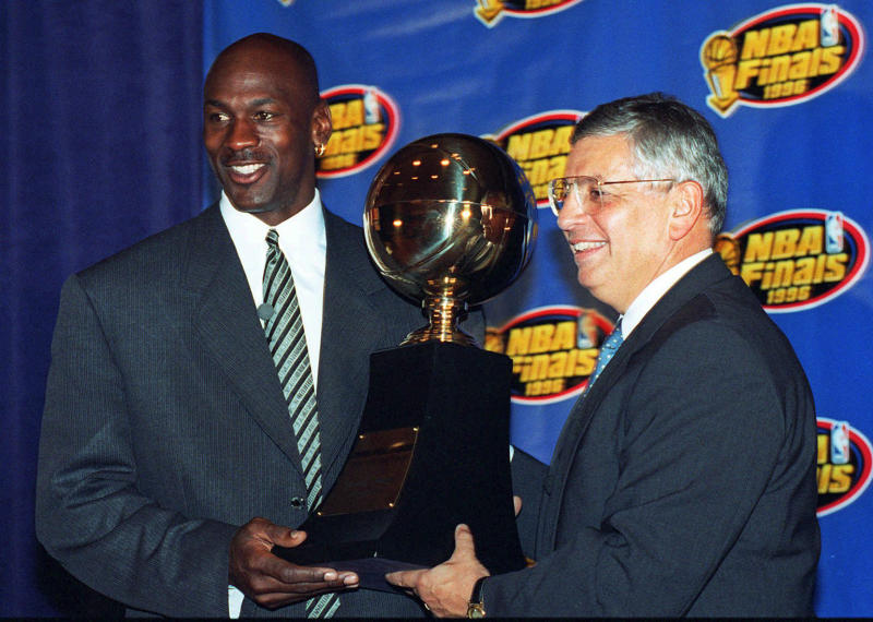 FILE - In this June 18, 1996, file photo, Chicago Bulls' Michael Jordan, left, receives the NBA Finals Most Valuable Player trophy from Commissioner David Stern during a ceremony in Chicago. The Bulls defeated the Seattle SuperSonics June 16 to win the basketball title. Stern announced during a news conference Thursday, Oct. 25, 2012, that he will retire on Feb. 1, 2014, 30 years after he took charge of the league. He will be replaced by Deputy Commissioner Adam Silver. (AP Photo/Charles Bennett, File)