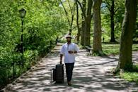 Herman James pulls his mobile barber kit in Central Park on May 6, 2021