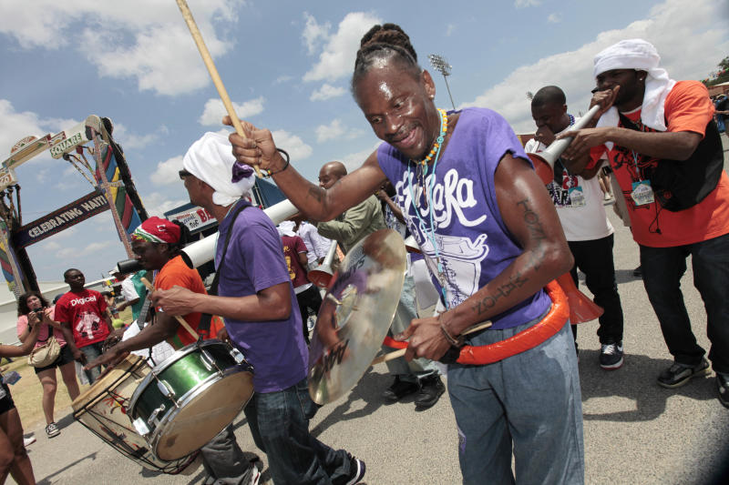 Members of the Haitian band DJA-Rara perform as they march through the fairgrounds at the Louisiana Jazz and Heritage Festival in New Orleans, Sunday, May 1, 2011. (AP Photo/Gerald Herbert)