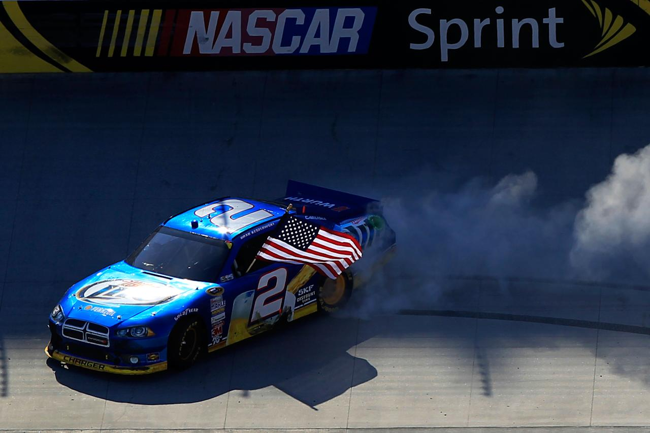 BRISTOL, TN - MARCH 18:  Brad Keselowski, driver of the #2 Miller Lite Dodge, and crew members celebrate with the American Flag and a burnout after winning the NASCAR Sprint Cup Series Food City 500 at Bristol Motor Speedway on March 18, 2012 in Bristol, Tennessee.  (Photo by Chris Trotman/Getty Images)