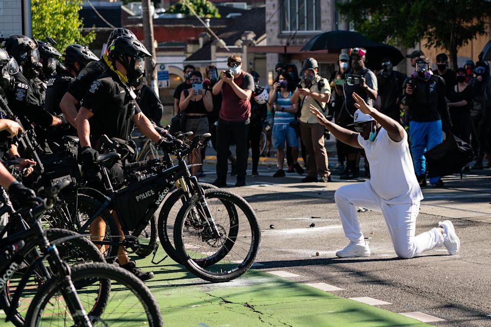 A demonstrator kneels in front of police during protests on Saturday. Source: Getty Images