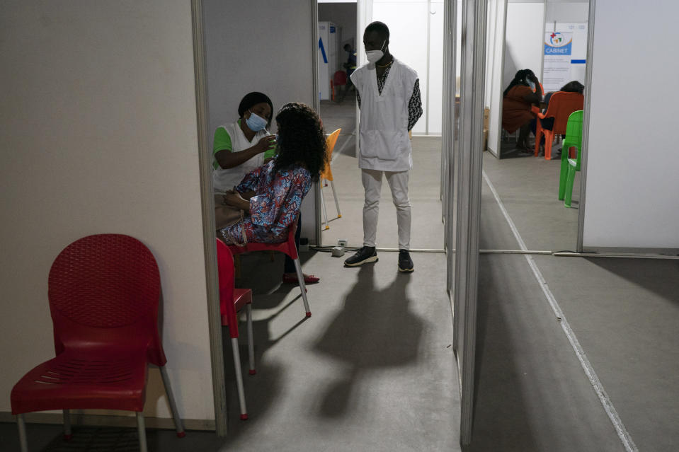 A health worker administers a dose of the AstraZeneca vaccine at the sport park of Treichville in Abidjan, Ivory Coast, Wednesday, June 16, 2021. Africa's 1.3 billion people account for 18% of the world's population. But the continent has received only 2% of all vaccine doses administered globally. (AP Photo/Leo Correa)