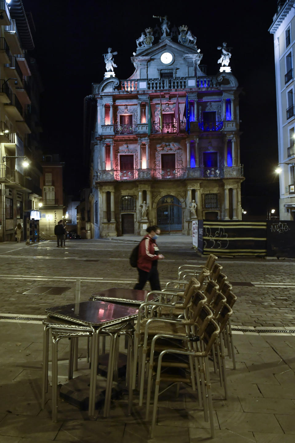 A resident wearing face mask protection walks along an empty Ayuntamiento square, in Pamplona, northern Spain, Saturday, Oct. 24, 2020, as new measures against the coronavirus began in the Navarra province where all bar and restaurants are closed for 15 days from midnight Wednesday. (AP Photo/Alvaro Barrientos)
