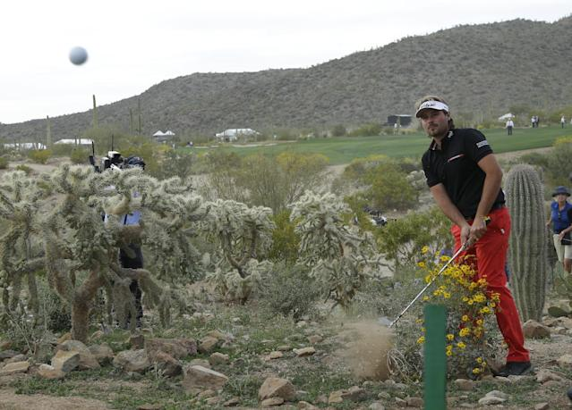 Victor Dubuisson, of France, hits out of the desert on the 20th hole in his championship match against Jason Day, of Australia, during the Match Play Championship golf tournament on Sunday, Feb. 23, 2014, in Marana, Ariz. (AP Photo/Ted S. Warren)