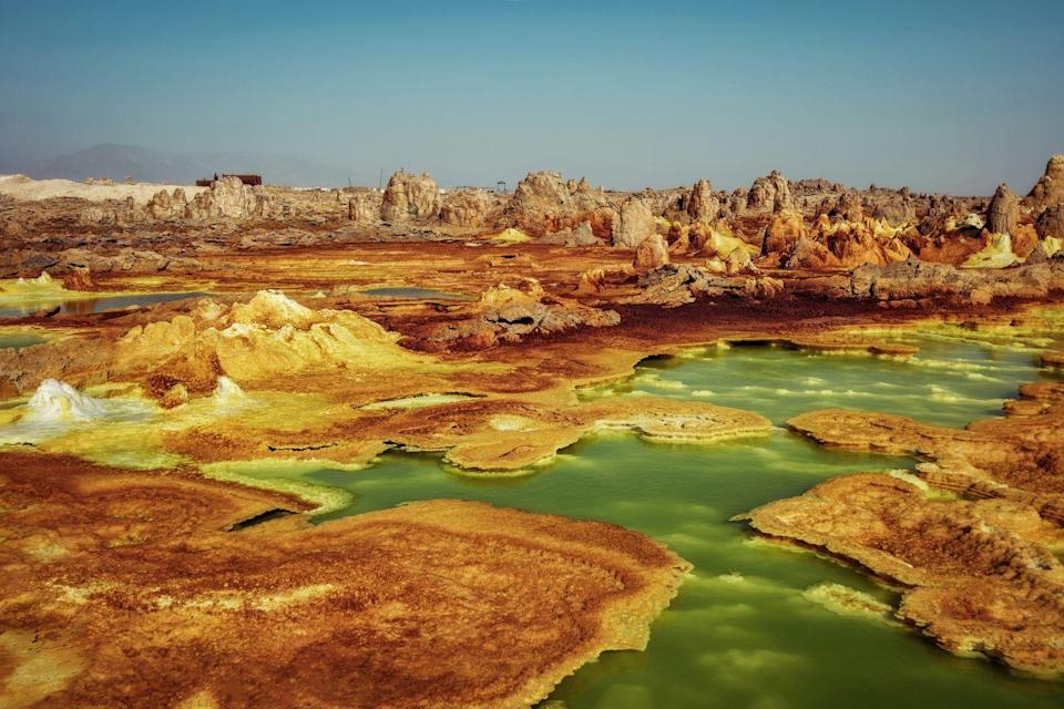 <p>Mounds of iron- and sulphur-rich salt in electric shades and slow bubbling pools assert an otherwordly beauty to Ethiopia's Dallol village and volcano. With annual temperatures averaging 94 degrees Fahrenheit, Dallol is considered one of the hottest places on Earth, making it inhabitable for most creatures. It's believed the volcano only formed in 1926, with it's hydrothermal system of small geysers, highly acidic springs, and mushrooms of salt. <br><br>Because the area can reach temperatures well into the 100s, it's advised to only visit during the cooler months, between October and February. Many scientists travel to the volcanic area during that time to study the hydrothermal system, which is thought to be similar to the landscape on Mars.</p>