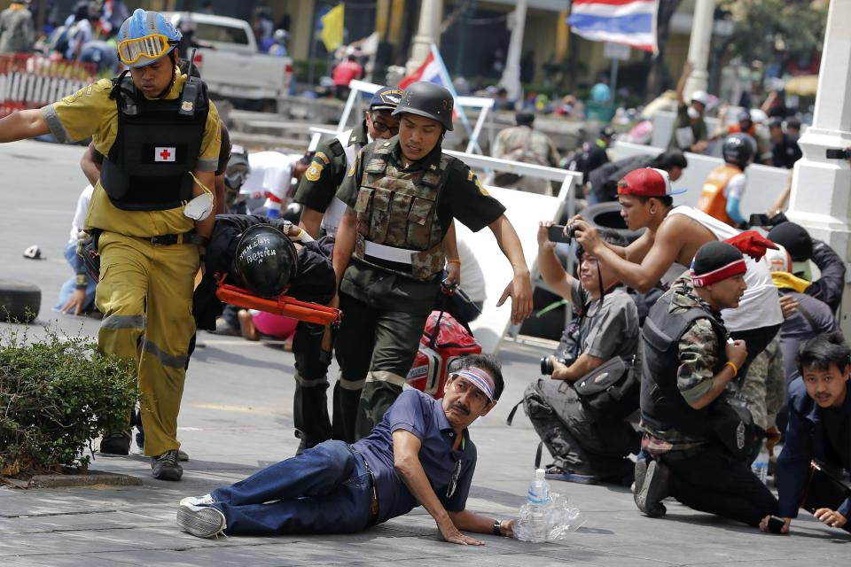 Anti-government protesters take cover as a wounded person is carried during clashes with the police near the Government House in Bangkok February 18, 2014. A Thai police officer was killed and dozens of police and anti-government protesters were wounded in gun battles and clashes in Bangkok on Tuesday, officials and witnesses said. REUTERS/Damir Sagolj (THAILAND - Tags: SOCIETY CIVIL UNREST POLITICS)