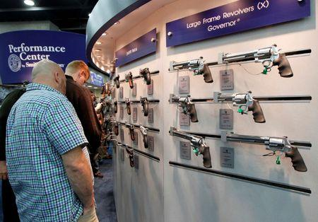 Gun enthusiasts look over Smith & Wesson guns at the National Rifle Association's annual meetings and exhibits show in Louisville