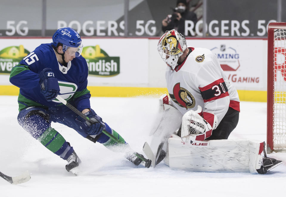 Ottawa Senators goalie Matt Murray (30) stops Vancouver Canucks' Matthew Highmore (15) during the second period of an NHL hockey game in Vancouver, British Columbia, Thursday, April 22, 2021. (Darryl Dyck/The Canadian Press via AP)