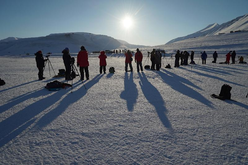 People watch the partial phase of a total solar eclipse from Longyearbyen, Svalbard, an archipeligo administered by Norway, on March 20, 2015 (AFP Photo/Stan Honda)