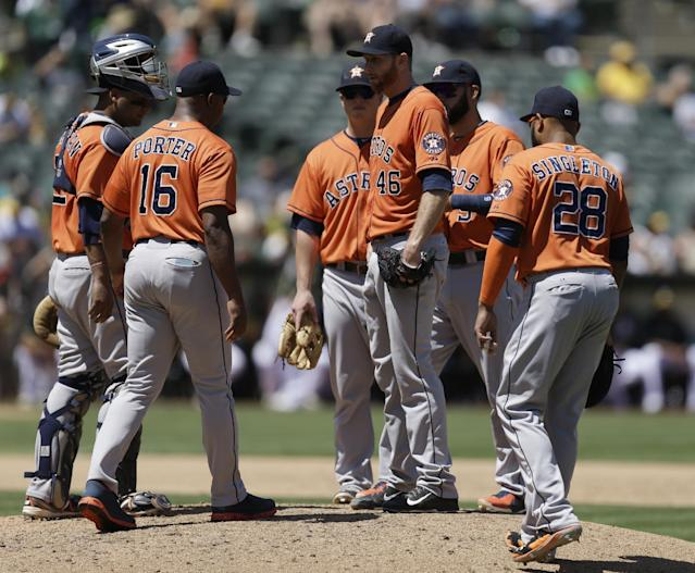 Houston Astros' Scott Feldman (46) waits for manager Bo Porter (16) on the pitching mound prior to being removed from a baseball game against the Oakland Athletics in the sixth inning on Thursday, July 24, 2014, in Oakland, Calif. (AP Photo)