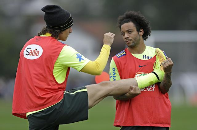Brazil's players Marcelo, right, and David Luiz exercise during a training session of the Brazilian national soccer team at the Granja Comary training center in Teresopolis, Brazil, Saturday, June 21, 2014. Brazil plays in group A of the 2014 soccer World Cup. (AP Photo/Andre Penner)
