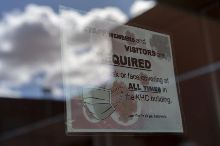 FILE - In this April 18, 2020, file photo, a sign on a door warns people to wear face coverings at the Kayenta Health Center on the Navajo reservation in Kayenta, Ariz. Across the nation, Native American tribes are working to protect their oldest members from the coronavirus. The effort is about more than protecting lives. (AP Photo/Carolyn Kaster, File)