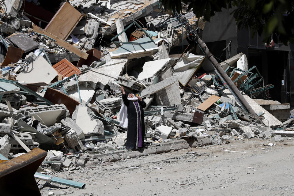 A woman reacts while standing on the rubble of a building that was destroyed by an Israeli airstrike on Saturday that housed The Associated Press, broadcaster Al-Jazeera and other media outlets, in Gaza City, Sunday, May 16, 2021. (AP Photo/Adel Hana)