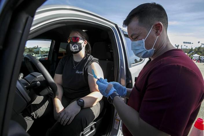 Los Angeles, CA - January 15: Dr. Richard Dang, right, Assistant professor USC School of Pharmacy administers COVID-19 vaccine to Ashley Van Dyke as mass-vaccination of healthcare workers takes place at Dodger Stadium on Friday, Jan. 15, 2021 in Los Angeles, CA. (Irfan Khan / Los Angeles Times)