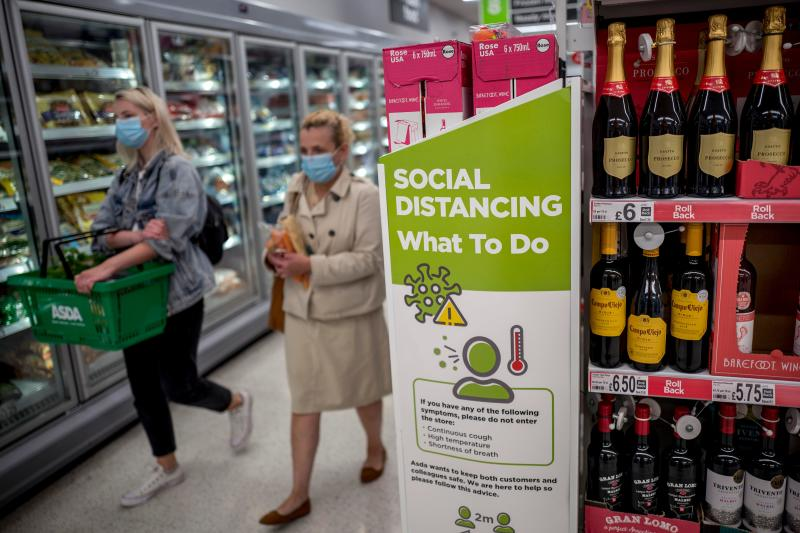 Shoppers wearing PPE (personal protective equipment), of a face mask or covering as a precautionary measure against spreading COVID-19,, walk past a banner advising customers to maintain the British government's current social distancing guidelines and stay two metres (2M) apart, inside an Asda supermarket store in Walthamstow, east London on June 22, 2020. - Britain's current social distancing guidelines set the distance between each person at two metres to avoid the risk of contamination to coronavirus. There is pressure on the government to reduce this distance in order to give a boost to bars, restaurants and hotels, which are scheduled to reopen next month. (Photo by Tolga AKMEN / AFP) (Photo by TOLGA AKMEN/AFP via Getty Images)