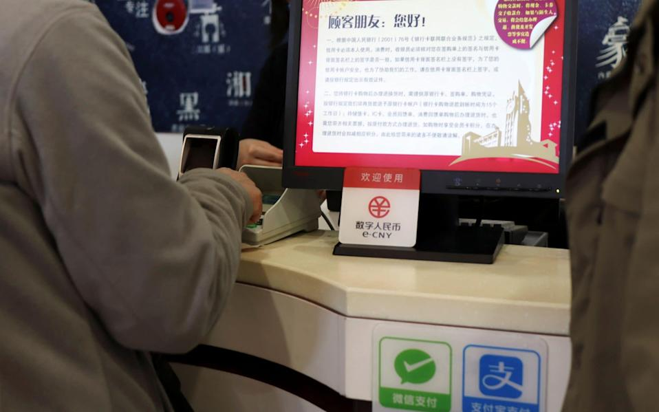 A sign advertising China's digital yuan is seen at a shopping mall in Beijing in February 2021 - FLORENCE LO/Reuters