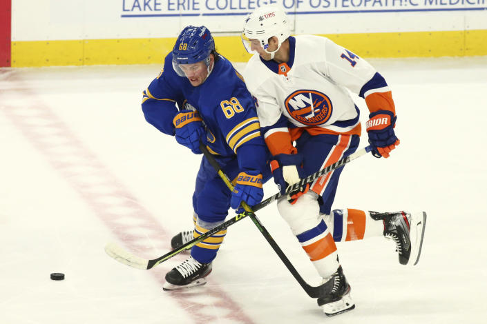 Buffalo Sabres forward Victor Olofsson (68) and New York Islanders forward Travis Zajac (14) battle for the puck during the first period of an NHL hockey game, Monday, May 3, 2021, in Buffalo, N.Y. (AP Photo/Jeffrey T. Barnes)