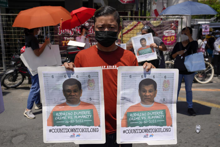A protester holds a banner showing pictures of Philippine President Rodrigo Duterte during a rally outside the Malacanang palace in Manila, Philippines on Wednesday, June 30, 2021. The group has called for justice and accountability for the thousands who have died due to the government's anti-drug crackdown under the Duterte administration. (AP Photo/Aaron Favila)