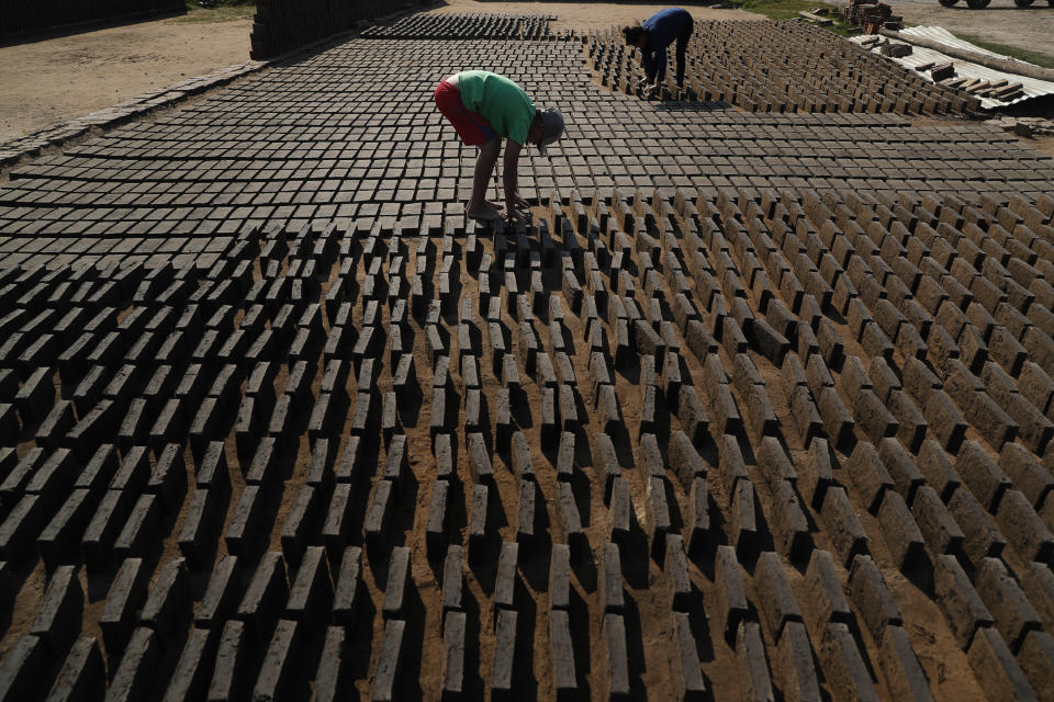 Cristian, center, turns clay bricks on their sides as they sun dry before they are put in a kiln at a small brick factory in Tobati, Paraguay, Monday, Aug. 24, 2020. While the government prohibits minors under 14 from working at brick factories, the 11-year-old said he's been working here to compliment his family's income, even before COVID-19 pandemic closed schools. (AP Photo/Jorge Saenz)