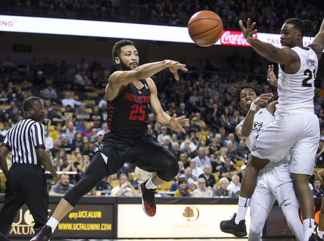 Houston guard Galen Robinson Jr. (25) passes the ball on Central Florida's guard Xavier Grant (12) during the first half of an NCAA college basketball game in Orlando, Fla., Thursday, Feb. 7, 2019. (AP Photo/Willie J. Allen Jr.)