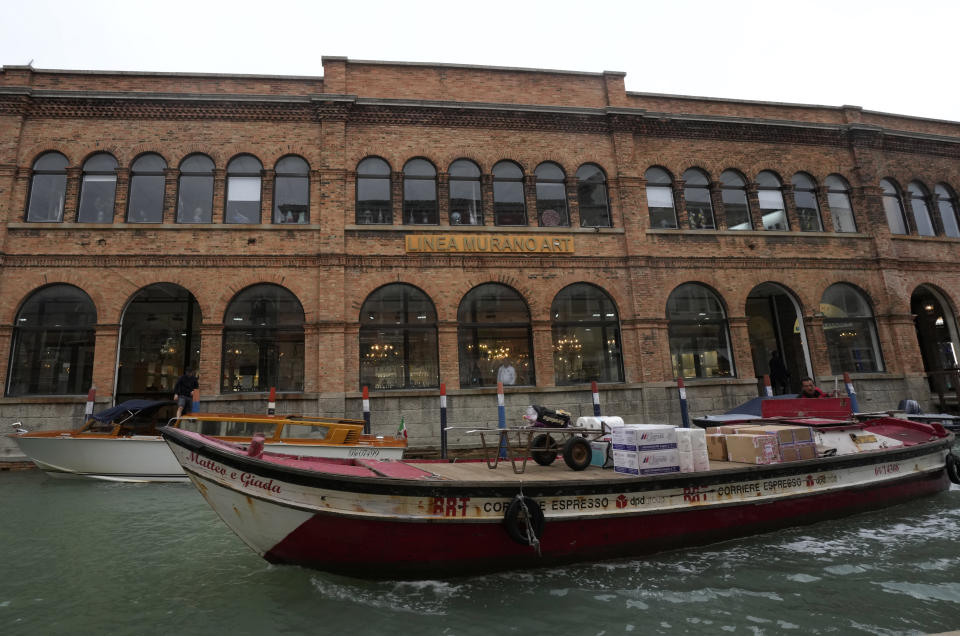 A boat sails past a historical artistic glass factory in Murano island, Venice, Italy, Thursday, Oct. 7, 2021. The glassblowers of Murano have survived plagues and pandemics and have transitioned to highly prized artistic creations to outrun competition from Asia, but surging energy prices may be their doom. (AP Photo/Antonio Calanni)