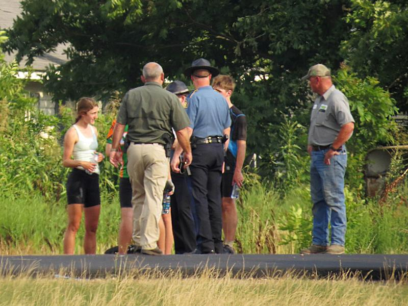 In this July 2, 2013, photo provided by Walter Breckenridge, authorities talk to bicyclists from a Massachusetts-based summer camp program following an accident in McCrory, Ark. Authorities say a car crashed into the group of 13 cyclists who were on a cross-country trip. A spokesperson for the program said three cyclists were airlifted to hospitals in Little Rock and Memphis, Tenn., while four other bicyclists were taken to local hospitals. Names have not been released and the car's driver wasn't injured. (AP Photo/Walter Breckenridge) MANDATORY CREDIT