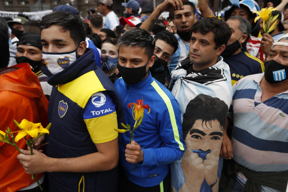 Soccer fans line up to see the casket with the body of Diego Maradona at the presidential palace in Buenos Aires, Argentina, Thursday, Nov. 26, 2020. The Argentine soccer great who was among the best players ever and who led his country to the 1986 World Cup title died from a heart attack at his home Wednesday, at the age of 60. (AP Photo/Natacha Pisarenko)