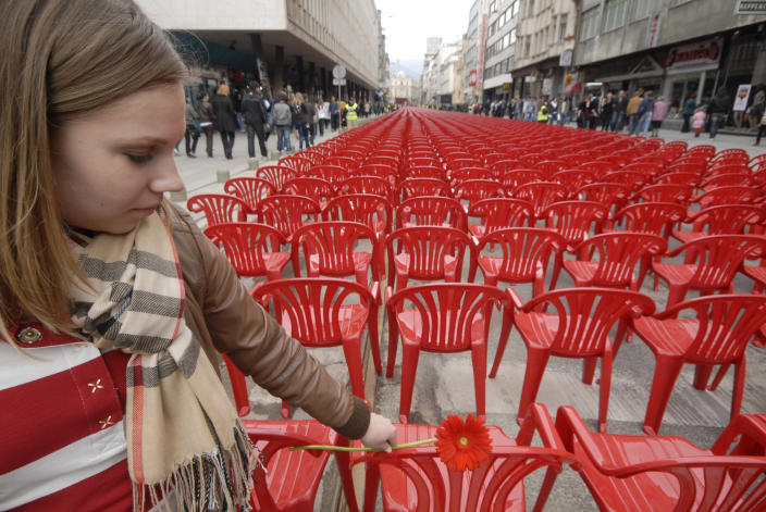 Bosnian girl lays flower on red chairs displayed along main street in Sarajevo to mark the 20th anniversary of the start of the Bosnian War on Friday, April 6 2012. City officials have lined up 11,541 red chairs arranged in 825 rows along the main street that now looks like a red river. Nobody will be sitting in them since the concert being held is for 11,541 Sarajevans who were killed during the siege.(AP Photo/Sulejman Omerbasic)