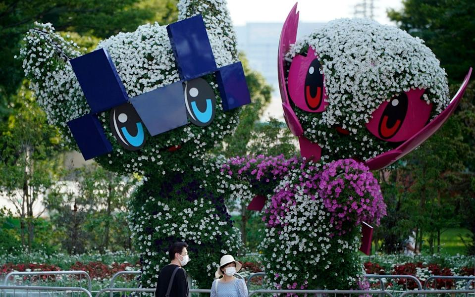 People wearing face masks stand before trees cut in the shape of the Tokyo 2020 Olympics mascots in Tokyo, Japan, 22 July 2021. Just a day before the opening ceremony, officials announced 1,979 new COVID-19 cases in the Japanese capital, the highest figure since January - FRANCK ROBICHON/EPA-EFE/Shutterstock