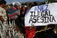 """People attend the funeral of supporters of former President Evo Morales killed during clashes next to a banner reading in Spanish """"Anez illegal killer"""" referring to Bolivia's interim President Jeanine Anez in Sacaba, Bolivia, Saturday, Nov. 16, 2019. Bolivian security forces clashed with Morales' supporters in a central town Friday, leaving at least five people dead, dozens more injured and escalating the challenge to the country's interim government to restore stability. (AP Photo/Juan Karita)"""