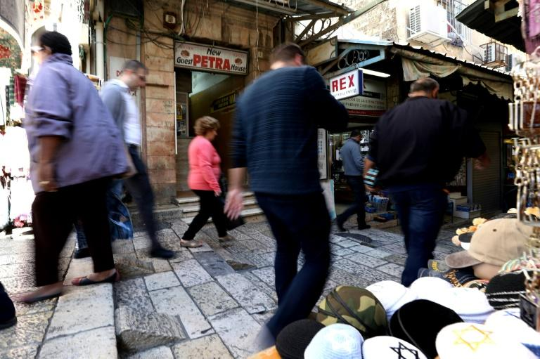People walk past the Petra guest house located next to Jaffa Gate in the Christian quarter of Jerusalem's Old City, one of three disputed properties allegedly sold to an Israeli settlers association (AFP Photo/GALI TIBBON)