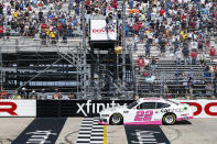 Austin Cindric takes the checkered flag as he crosses the finish line to win a NASCAR Xfinity Series auto race at Dover International Speedway, Saturday, May 15, 2021, in Dover, Del. (AP Photo/Chris Szagola)