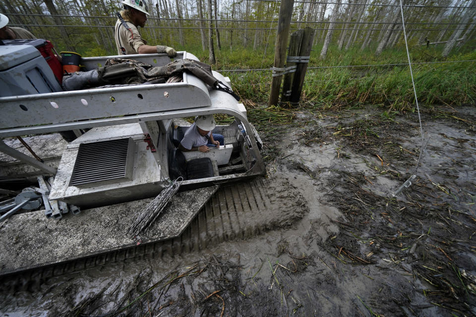 Electrical workers for Sparks Energy ride in a marsh buggy to restore power lines running through a marsh in the aftermath of Hurricane Ida in Houma, La., Friday, Sept. 17, 2021. The Louisiana terrain presents special challenges. In some areas, lines thread through thick swamps that can be accessed only by air boat or marsh buggy, which looks like a cross between a tank and a pontoon boat. Workers don waders to climb into muddy, chest-high waters home to alligators and water moccasins. (AP Photo/Gerald Herbert)