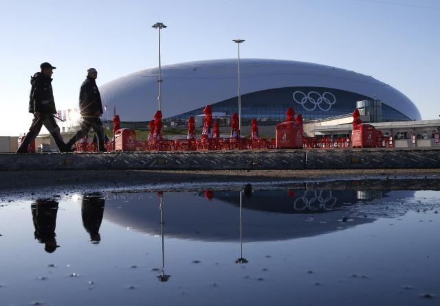 Two security personnel walk past the Bolshoy Ice Dome as preparations continue at the Olympic Park for the Sochi 2014 Winter Olympics