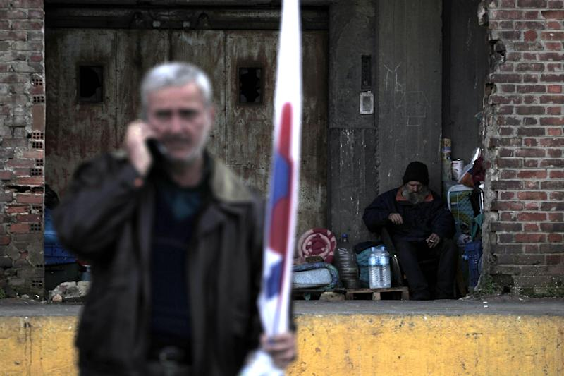 A member of a Communist Party-affiliated union talks on his phone as a homeless man sits under an abandoned warehouse during a demonstration in solidarity for mobilized ferry crews at Piraeus, the port of Athens, on Wednesday, Feb. 6, 2013. Greece's conservative-led government used emergency powers late Tuesday to order striking seamen back to work after a six-day walkout to protest pay arrears of over six months, benefit cuts and austerity measures. (AP Photo/Petros Giannakouris)
