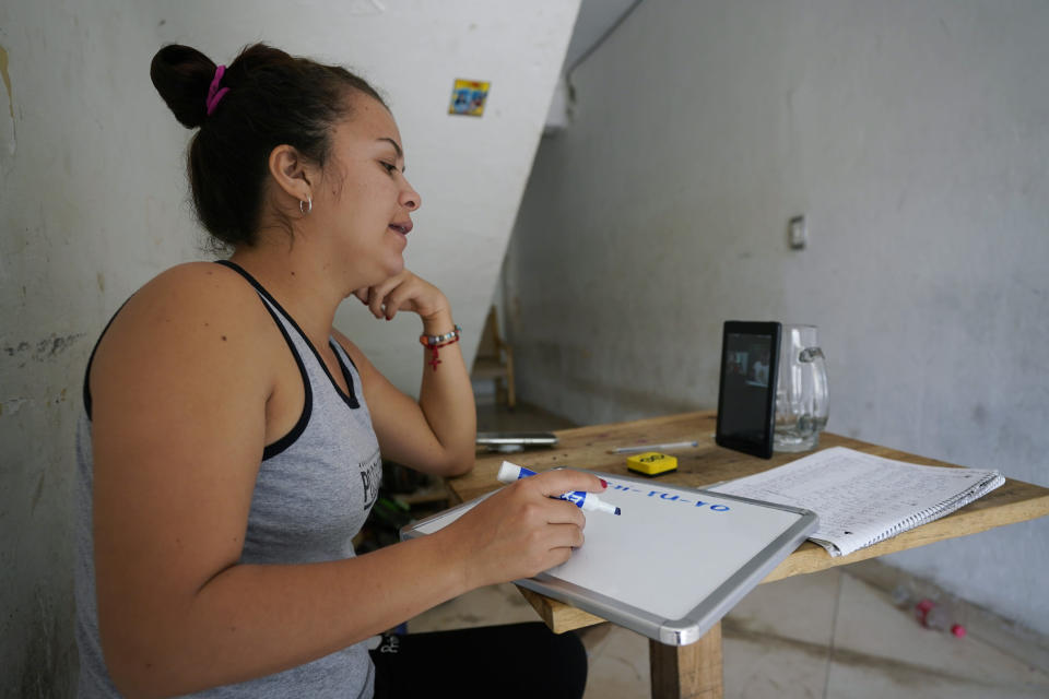 Gabriela Fajardo, a 26-year-old Honduran seeking asylum in the United States, teaches a Zoom class for Central American children living in camps, various shelters and apartments in other parts of Mexico from a hallway of an aged building in Matamoros, Mexico, on Friday, Nov. 20, 2020. Like countless schools, the sidewalk school went to virtual learning amid the coronavirus pandemic but instead of being hampered by the change, it has blossomed. (AP Photo/Eric Gay)