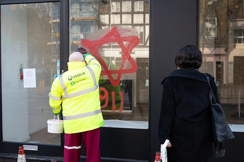 A council cleaner removes anti-semitic graffiti in the form of numbers, 9 11, and a Star of David, on a shop window in Belsize Park, North London.