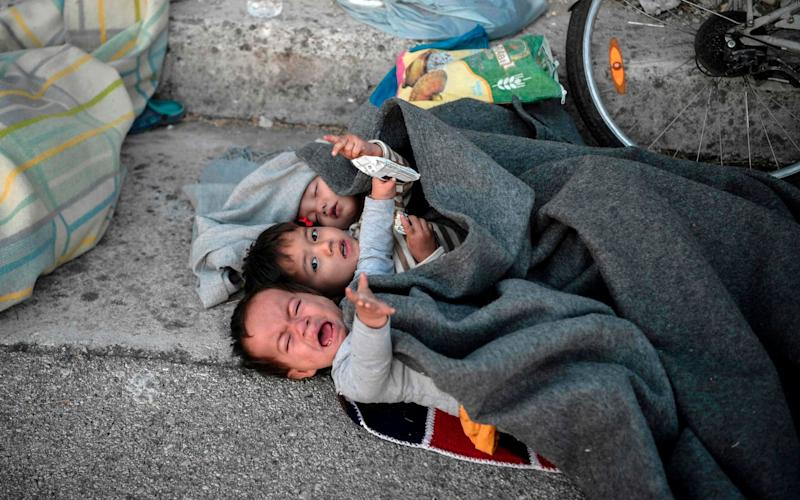 Children wake up after spending the night sleeping in a road - AFP