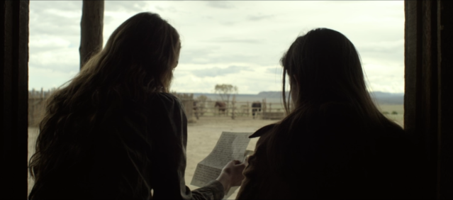 Alice (Michelle Dockery) and Truckee (Samuel Marty) sit in the doorway of their home. (Image: Netflix)