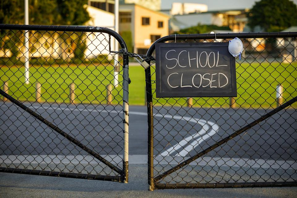 A closed-school sign on the gate.