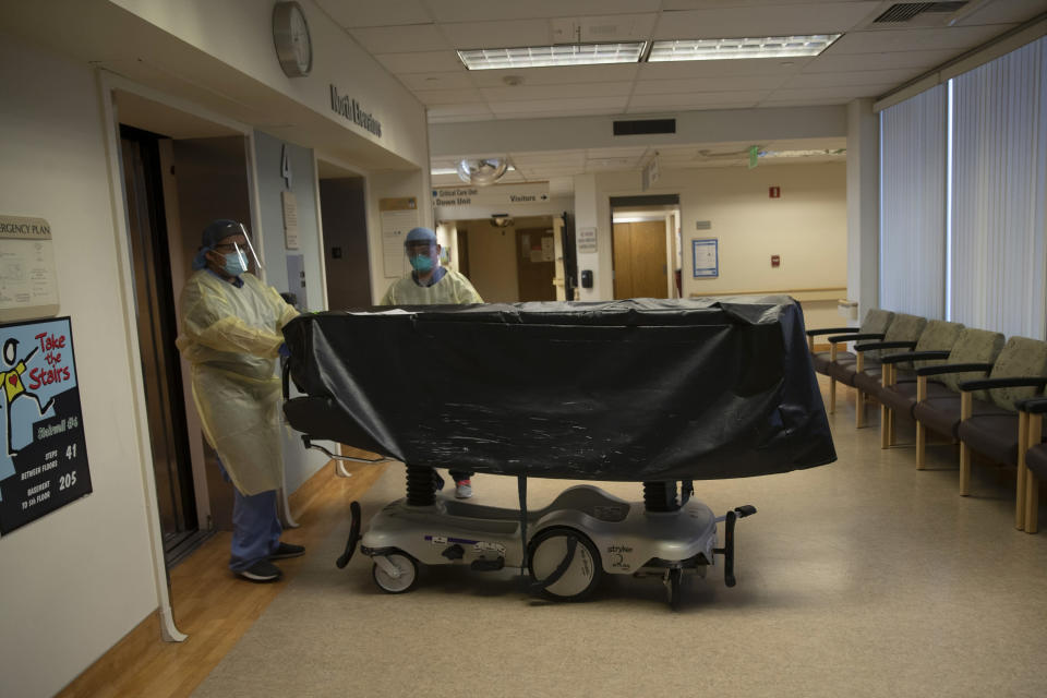 FILE - In this July 7, 2020, file photo, hospital staff members enter an elevator with the body of a COVID-19 victim on a gurney at St. Jude Medical Center in Fullerton, Calif. California health authorities reported on Saturday, Jan. 9, 2021, a record high of 695 coronavirus deaths as many hospitals strain under unprecedented caseloads. The state Department of Public Health says the number raises the state's death toll since the start of the pandemic to 29,233. (AP Photo/Jae C. Hong, File)