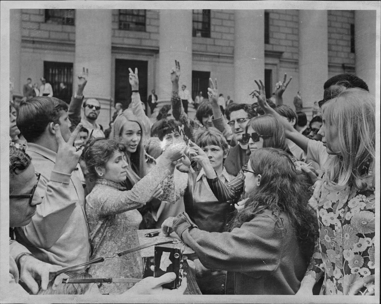 Several women protesters burn what they say are draft cards belonging to friend in a demonstration at the Federal court today in support of Dr. Benjamin Spock. Spock and three others were convicted in Boston Tuesday of conspiring to counsel young men to evade the draft. June 20, 1968.