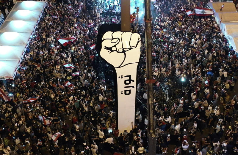 "In this photo from a drone, anti-government protesters re-install a new large cardboard fist labelled ""Revolution"" in Martyr's Square after a previous one was burned down overnight by unknown vandals, at the Martyr square, in downtown Beirut, Lebanon, Friday, Nov. 22, 2019. Lebanon's protesters and top politicians held competing Independence Day celebrations Friday, reflecting the deepening rift that has beset the country grappling with its worst political and economic crises in decades. (AP Photo/Hussein Malla)"